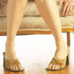 Woman legs sitting on couch